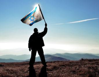 41934310 - successful silhouette man winner waving israel flag on top of the mountain peak